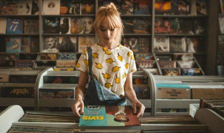 エルビスのレコードを手に取ってジャケットをしげしげと見つめるポニーテールの女性