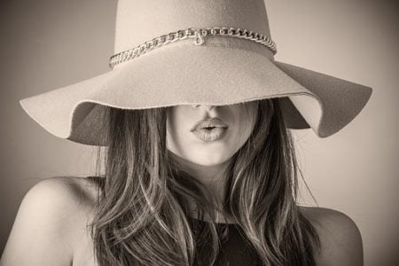 つばの広い麦わら帽子を目部下に被った女性の画像