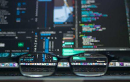 編集作業中のデスクの前に置かれた黒ぶちメガネとディスプレイのある風景
