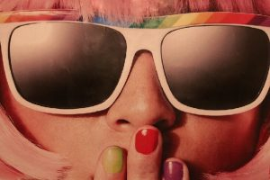 ピンクのかつらとサングラスをかけたポップな70年代風の女性の顔のアップ