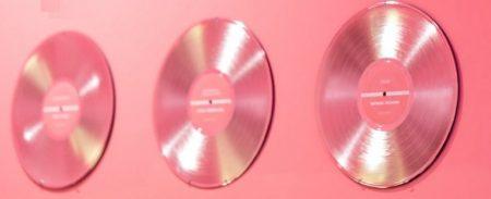 ピンクの壁に飾られた3つのDVDディスク