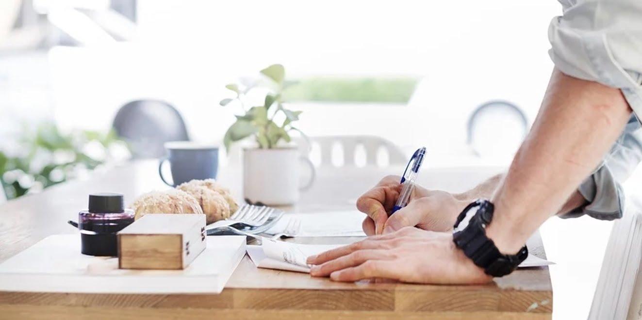 書類に書き込む男性の手元