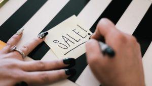 saleの文字をかく女性