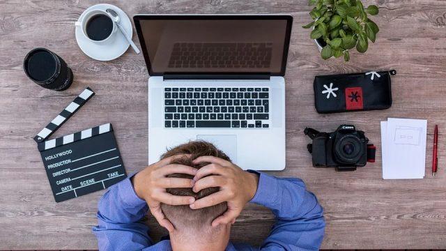 パソコンの前で頭を抱える男性の風景