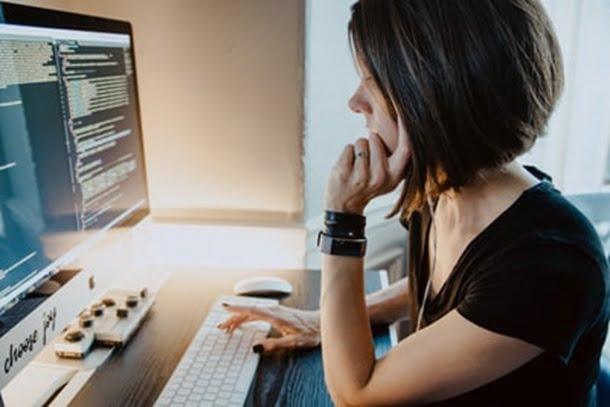 左の肘をついて、パソコンに向き合う女性を横から見た画像