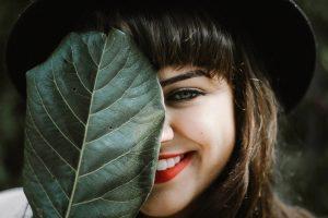 葉で片目を隠しこちらを見て微笑む女性