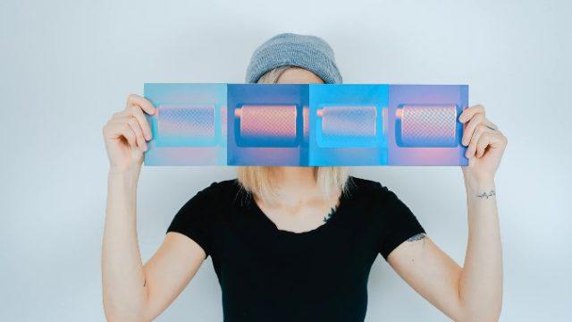 クリアフィルムを目のまえにかざして顔を隠している女性