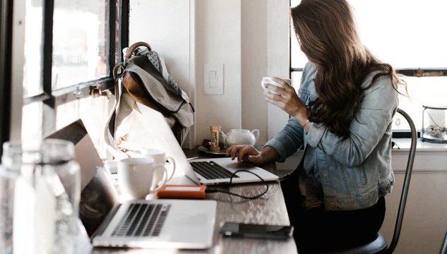 カフェでノートパソコンを使った作業をする女性