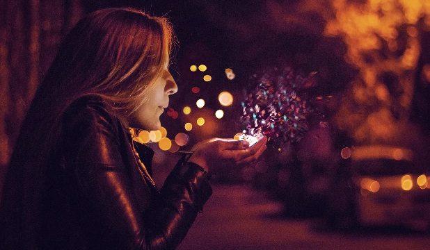 手のひらにある光の粉に息を吹きかけて舞い散らせる髪の長い女性の横顔