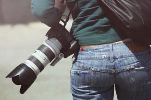 一眼レフカメラを提げた女性の後ろ姿