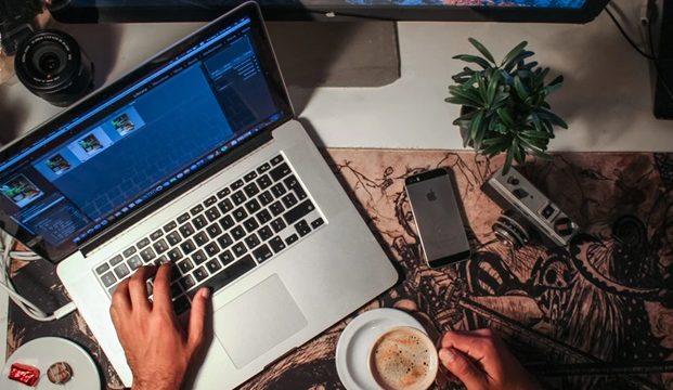コーヒー片手に、大型ディスプレイとノートパソコンとスマホを楽しむ男性のひと時