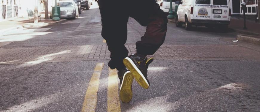 アスファルトの上でジャンプする男性の足元