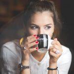 人_マグカップに口をつけながら未来を予想しながら視線を外す女性