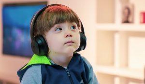 ヘッドフォンを耳にかけて、疑問を感じながら斜め上を見ている男の子