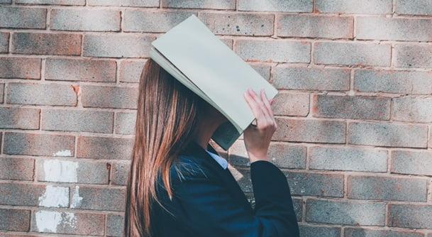 本で顔を覆って思考する女性