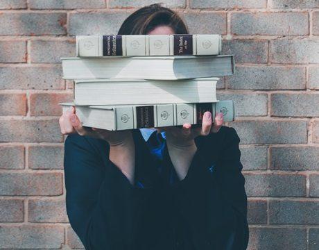 顔の前に本を積み上げて表情が見えなくなった女性