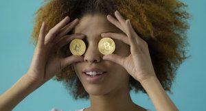 ビットコインを両目にそえて、おどけた表情をする女性