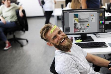 オフィスでおでこに付箋を貼り、おどけて笑う男性