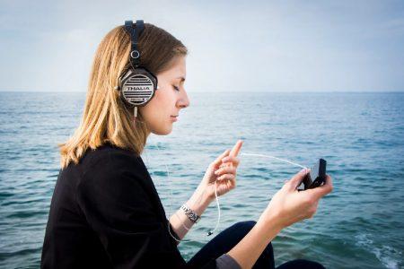 海辺で音楽鑑賞をする女性