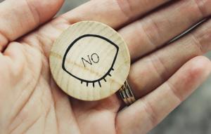 掌に置かれた目のアイコンを象った木彫りのNOマーク