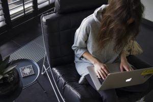 ソファーにすわり、膝の上にノートパソコンを載せて作業をする女性