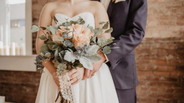 結婚式でブーケを持つ花嫁を後ろから抱きしめる新郎の画像