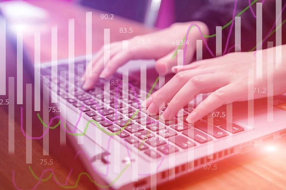 インターネット回線のイメージ ノートパソコンをタイプする手とグラフ・チャートをオーバーレイした画像