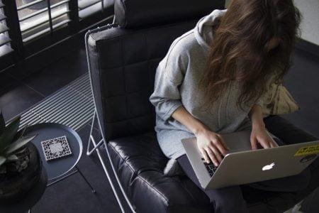 膝の上にノートパソコンを置いてソファーで作業をする女性