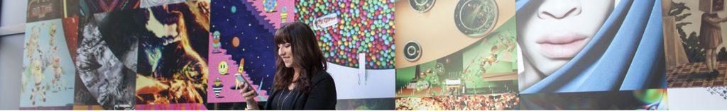 adobeの本社のロビーで作品を前にスマホを操作する女性のいる風景
