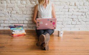 壁にもたれてパソコンで勉強する女性