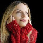 真っ赤なセーターを着て、遠くを眺めるブロンドの女性