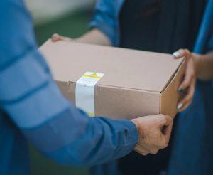 荷物を手渡しで届けてくれる宅配の男性と、受け取る女性