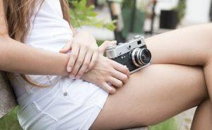 ベンチに座って右手にコンパクトデジカメを持ち、膝に抱える女性