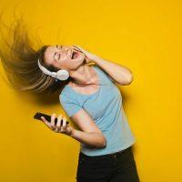人_黄色い壁の前で、ヘッドフォンを抱えてヘッドバンキングしている女性の画像