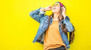 人_黄色い壁の前でヘッドフォンをかけて空を見上げるジージャンを着た女性