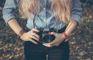 カメラ_を首から下げたカジュアルな女性の画像