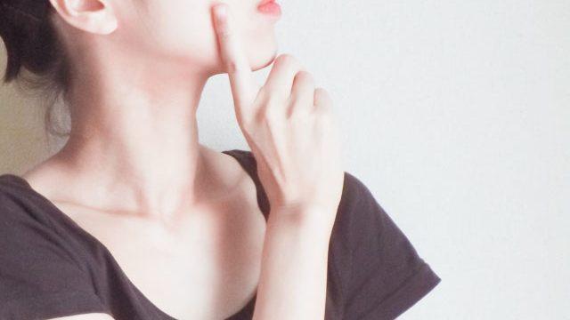 人差し指を頬にあてて考え込む女性の横顔